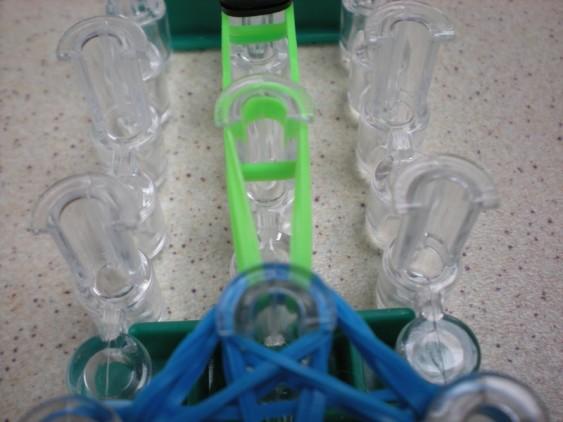 Схема плетения черепашки на станке - пара зеленых резинок перетянута на один столбик